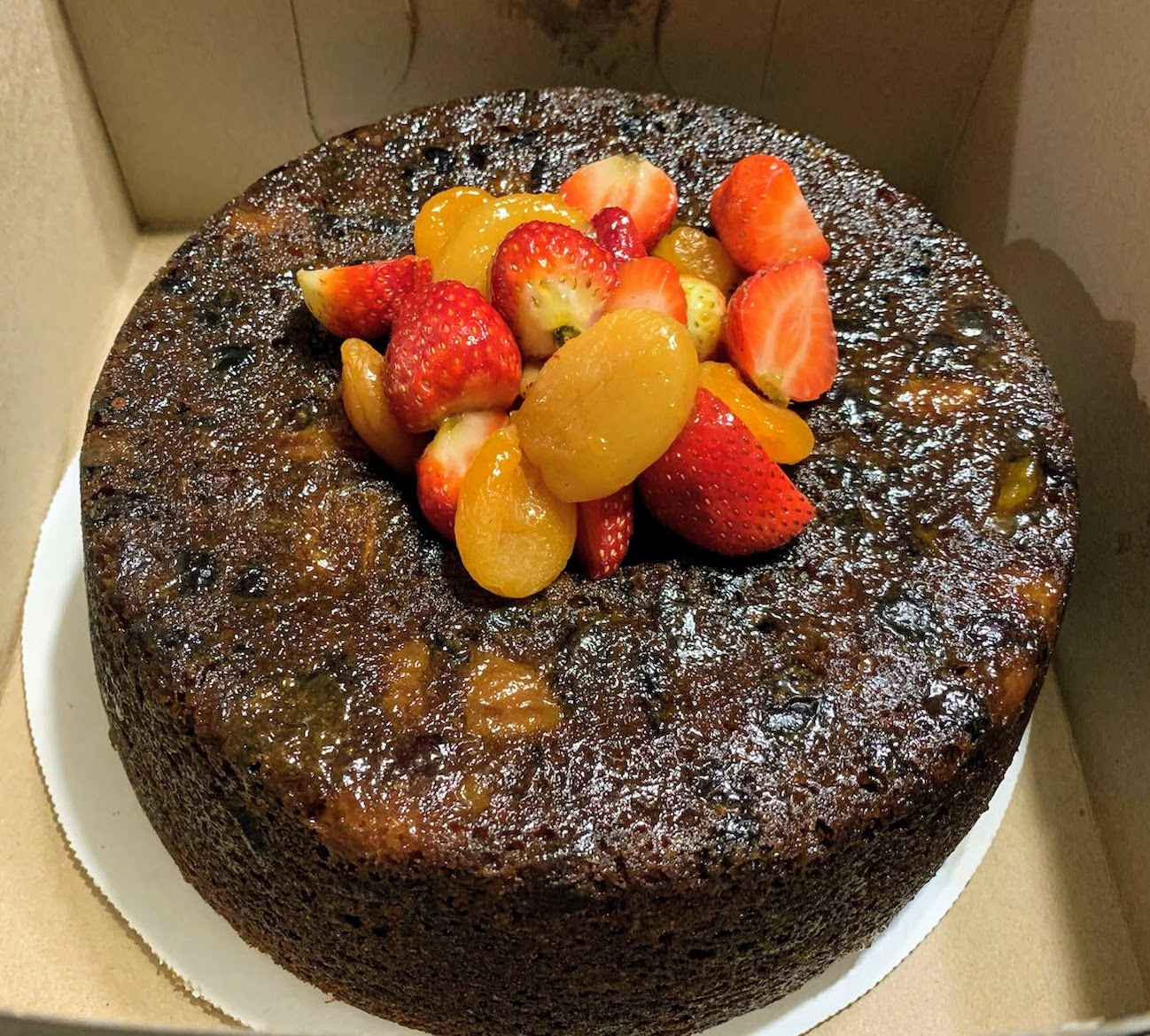 Dark fruitcake with strawberries and apricots on top