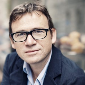 White man with brown hair and dark rimmed glasses