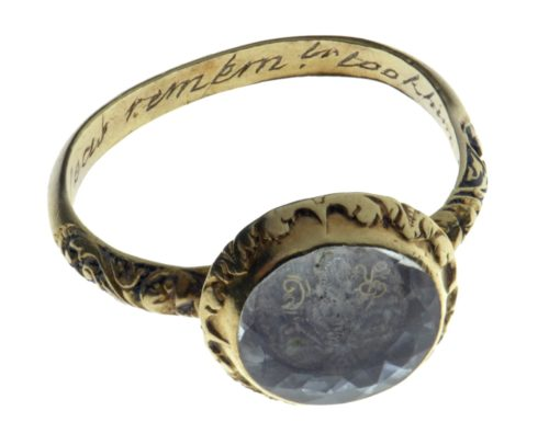 Photograph of a gold ring with blue stone and inscription in the band