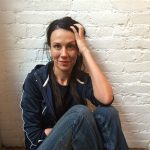 Rivka Galchen sits against a white brick wall with one hand in her hair